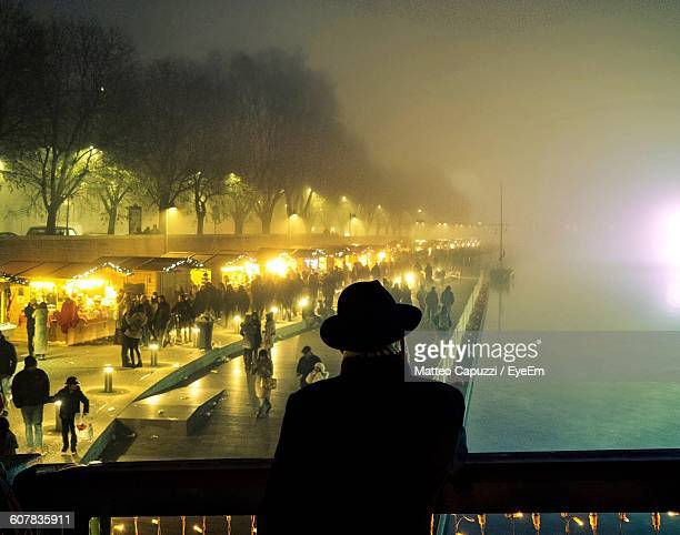 people enjoying at illuminated christmas market during foggy weather - mere noel stock pictures, royalty-free photos & images