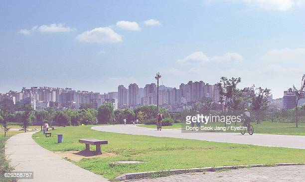 People Enjoying At Park By City Against Sky