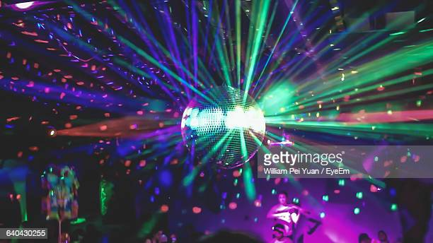 people enjoying below illuminated disco ball at nightclub - disco ball fotografías e imágenes de stock