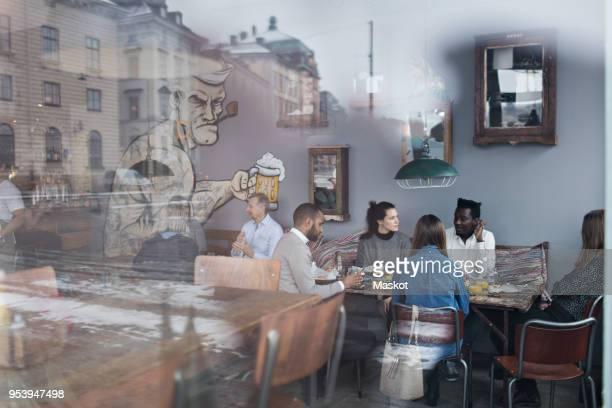 people enjoying brunch at restaurant seen through glass window - stockholm stock-fotos und bilder