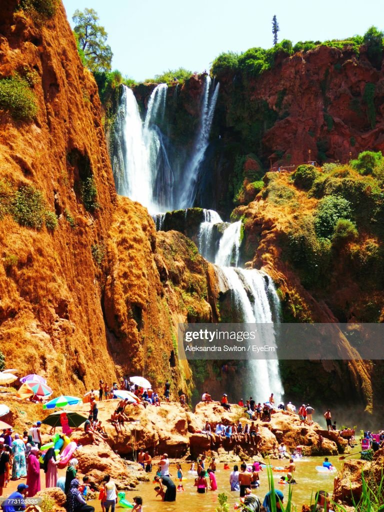 People Enjoying By Waterfall Against Sky : Photo
