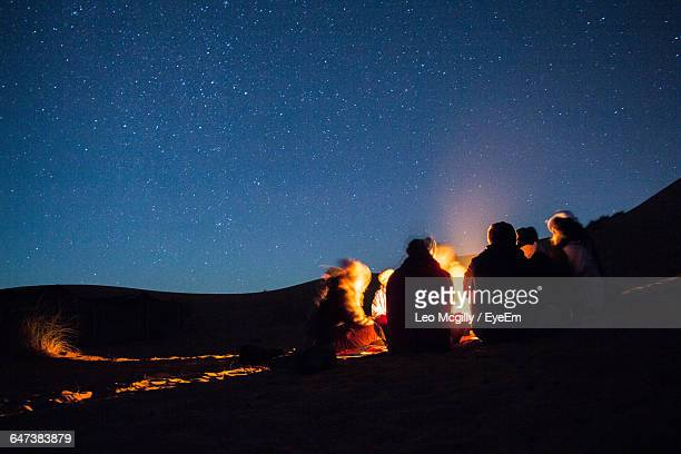 people enjoying campfire in desert at night - campfire stock pictures, royalty-free photos & images