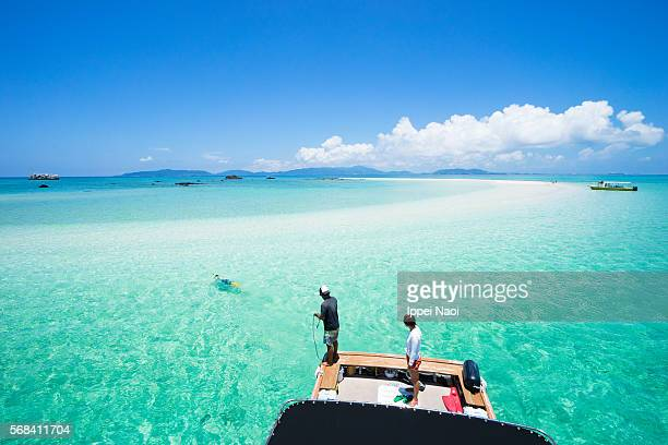People enjoying clear tropical water and coral cay, Sekisei Lagoon, Japan
