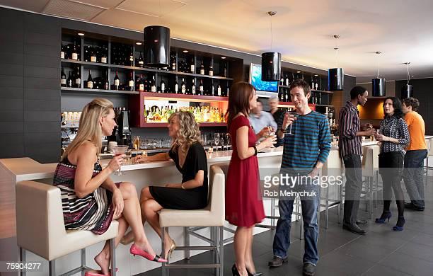 People enjoying cocktails at bar