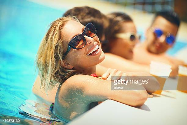 people enjoying drinks by the swimming pool. - pool party stock pictures, royalty-free photos & images