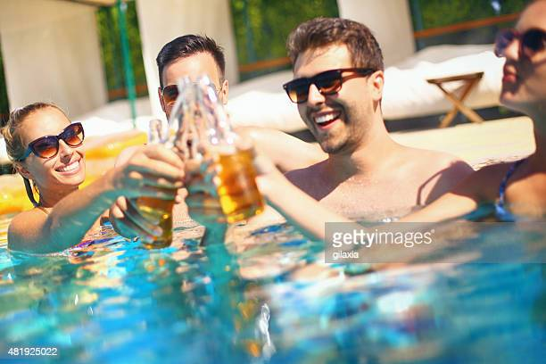 People enjoying drinks by the swimming pool.