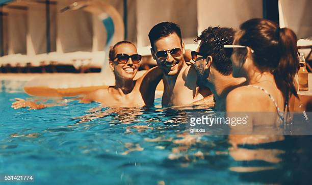 people enjoying drinks by the swimming pool. - poolside stock pictures, royalty-free photos & images