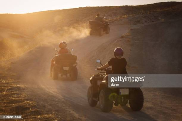 people enjoying driving atv on sunset in valleys of cappadocia with lot of dusts in background. - ネヴシェヒル県 ストックフォトと画像