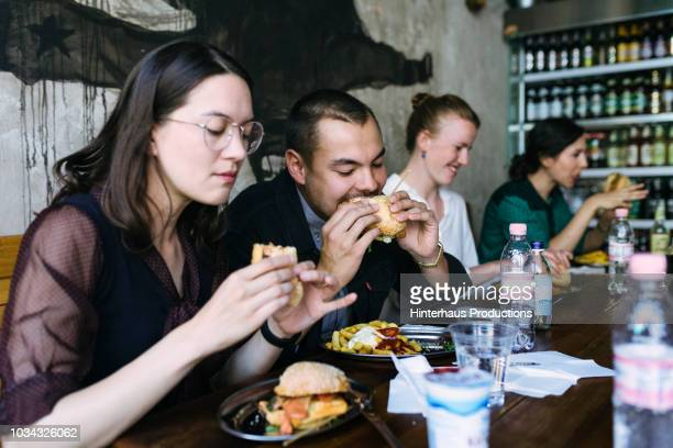 people enjoying food in burger restaurant - side by side stock photos and pictures