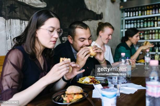 people enjoying food in burger restaurant - schlechte angewohnheit stock-fotos und bilder
