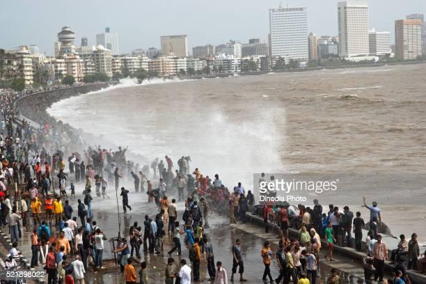 People enjoying hightide waves at marine drive Bombay, Mumbai, Maharashtra, India