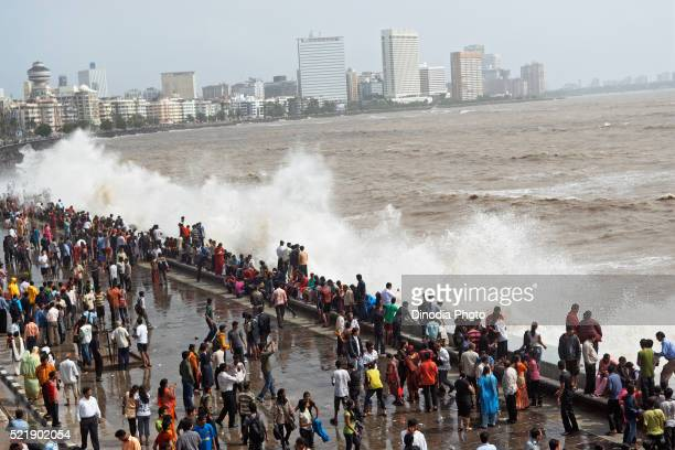 People enjoying hightide waves at marine drive Bombay, Mumbai, Maharashtra, India