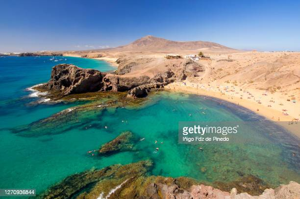 people enjoying in papagayo beach, lanzarote, canary islands, spain. - lanzarote stock pictures, royalty-free photos & images