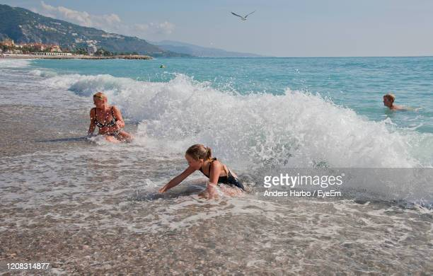 people enjoying in sea against sky - sea swimming stock pictures, royalty-free photos & images