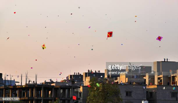 people enjoying kite flying on uttrayan (makar sankranti), ahmedabad, gujarat, india - ahmedabad stock pictures, royalty-free photos & images