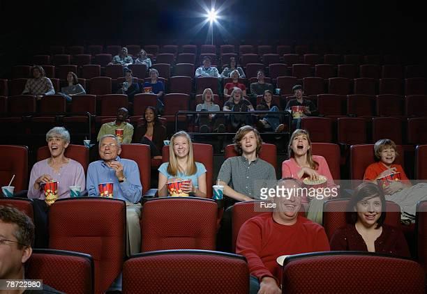 People Enjoying Movie in Movie Theatre