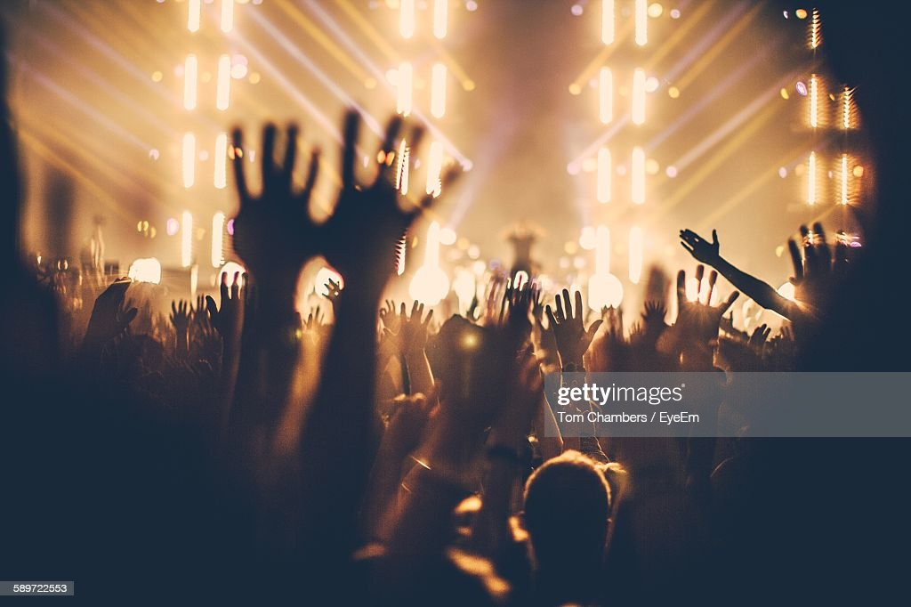 People Enjoying Music Concert With Hands Raised At Night : Stock Photo