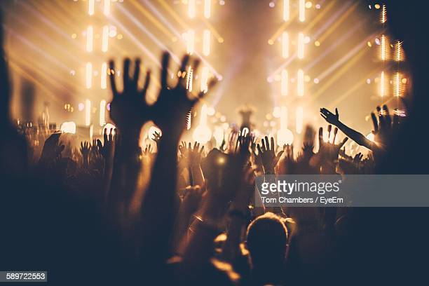 people enjoying music concert with hands raised at night - music festival photos et images de collection