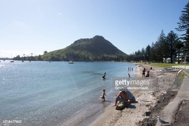 People enjoying on a beach under the Mount Maunganui in Tauranga North Island New Zealand October 30 2017