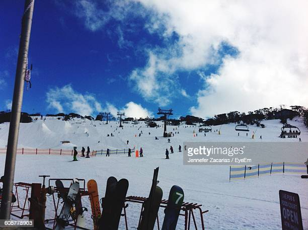 People Enjoying On Snowcapped Mountain Against Sky