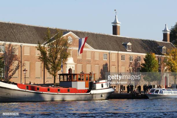 People enjoying on the banks of the Amstel river in Amsterdam