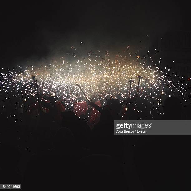 People Enjoying Party With Firework Display At Night