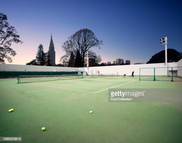 People enjoying playing tennis at an urban park in Tokyo, Japan