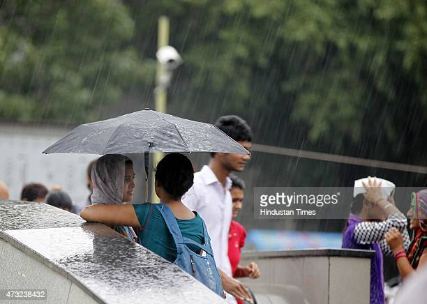 People enjoying pleasant weather during sudden rains as they got respite from scorching weather on May 13 2015 in New Delhi India Sudden rains...