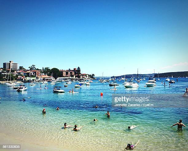People Enjoying Summer On Manly Beach Against Clear Blue Sky