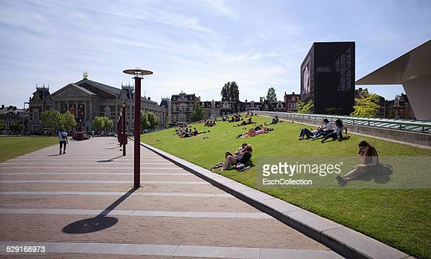 people enjoying sun at museumplein in amsterdam - museumplein stock pictures, royalty-free photos & images