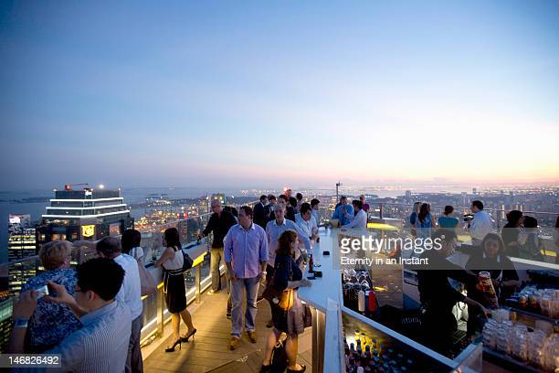 People enjoying sunset from rooftop bar