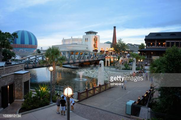 people enjoying the disney springs shopping and restaurant area - orlando florida stock pictures, royalty-free photos & images