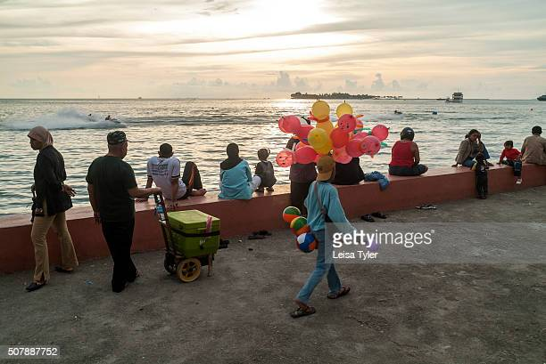 People enjoying the evening at the waterfront in the city of Makassar on Sulawesi, Indonesia.