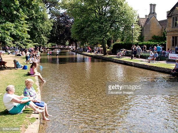 People enjoying the summer heat wave by the River Windrush BourtonontheWater Gloucestershire UK