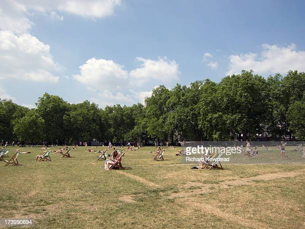 People enjoying the summer sun in Green Park, London, 13th July 2013