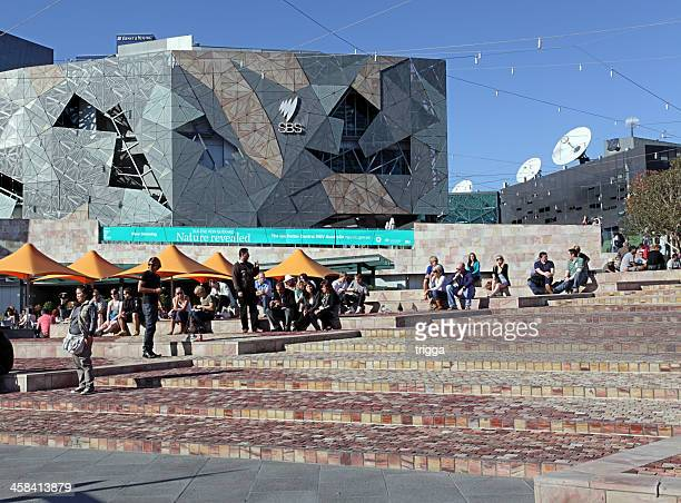 people enjoying the sunshine in federation square, melbourne, australia - federation square stock pictures, royalty-free photos & images