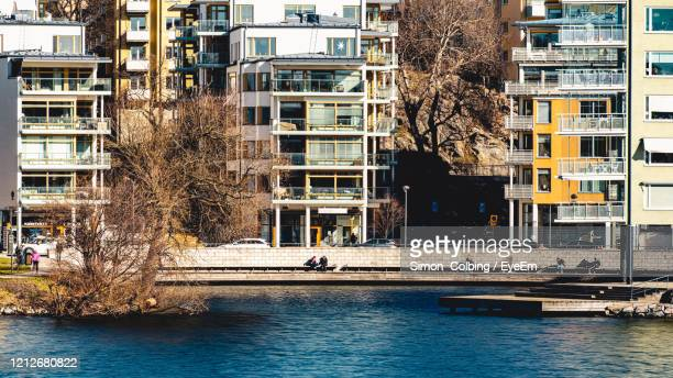 people enjoying the warming sun by the river a cold spring day - colbing stock pictures, royalty-free photos & images