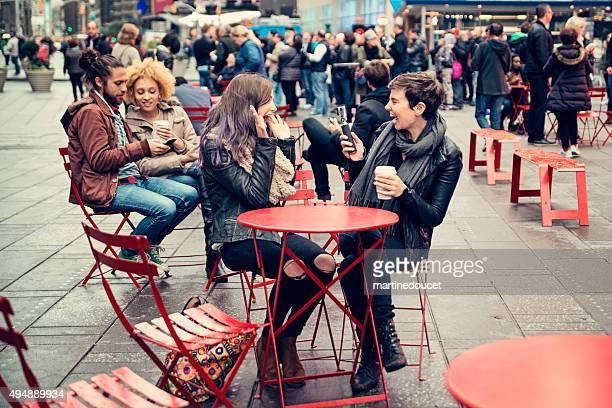 La gente disfruta de sí mismos en Times Square rojo sillas.