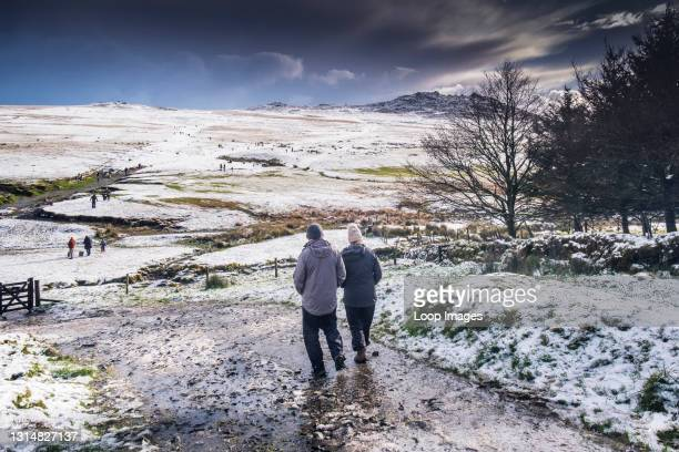 People enjoying walking in the snow on the wild rugged Rough Tor on Bodmin Moor in Cornwall.