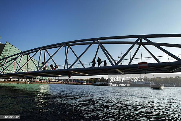 people enjoyong over the bridge in amsterdam - nemo museum stock pictures, royalty-free photos & images
