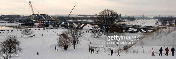 People enjoythe snow ast the arch of the Waldschloesschen Bridge is put in by floating pontoons on the river Elbe at the construction site in Dresden...