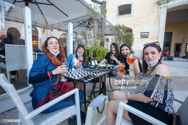 People enjpy drinks at a bar on May 23 2020 in Matera Italy Restaurants bars cafes hairdressers and other shops have reopened subject to social...