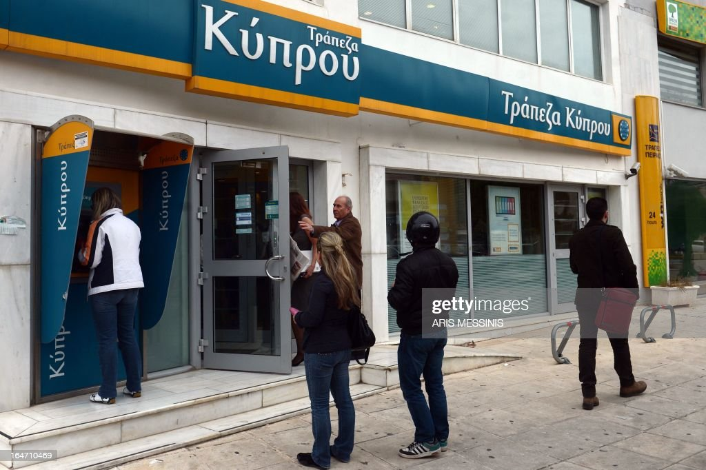 People enter a Bank of Cyprus branch in Athens on March 27, 2013, as Greek subsidiaries of three Cypriot banks reopened today after Greece's third lender, Piraeus bank, signed an agreement to acquire all their deposits, loans and branches. But banks in Cyprus itself remained closed as authorities worked out a plan to get them back up and running amid the country's financial crisis.