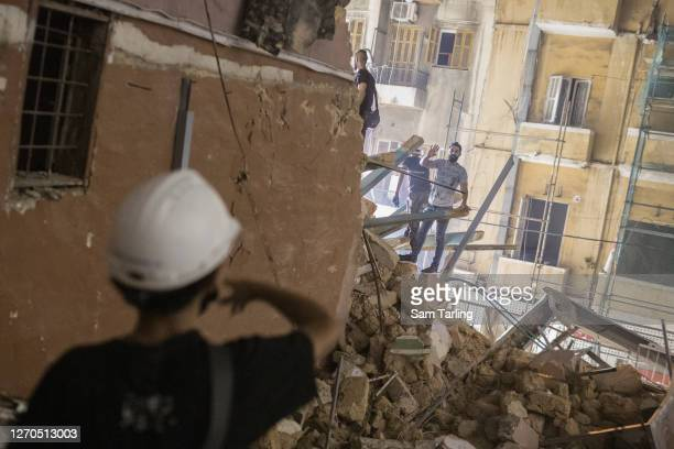 People enter a destroyed building with the aim of finding a potential survivor of the Beirut blast after rescue workers paused operations, on...