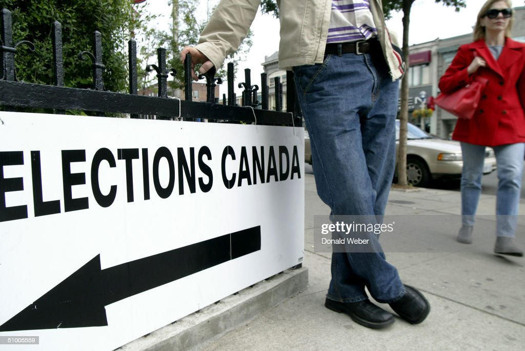 People enter a polling station to vote in the federal election to determine the next prime inister of Canada on June 28, 2004 in Toronto, Canada. The ruling party of Paul Martin's Liberals and the Stephen Harper led Conservative party are tied neck and neck in recent polls, leading to a possible minority government.