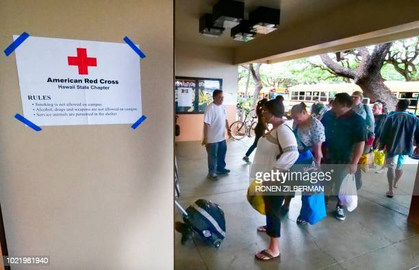 People enter a Red Cross shelter at McKinley High School ahead of the arrival of hurricane Lane in Honolulu Hawaii on August 23 2018 Hurricane Lane...