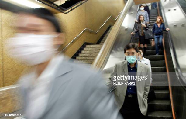 People enter a station of Hong Kong's Mass Transit Railway wearing masks to protect against a killer outbreak of pneumonia which shows no sign of...