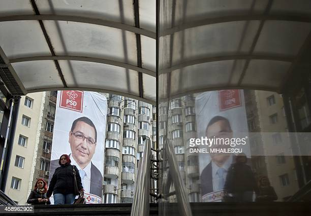 People enter a subway station backdropped by a banner advertising Romanian Prime Minister and presidential candidate Victor Ponta in Bucharest on...