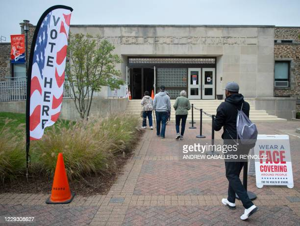 People enter an auditorium at Morgan State University to vote, on the second day of early voting in the US presidential race, in Baltimore, Maryland...