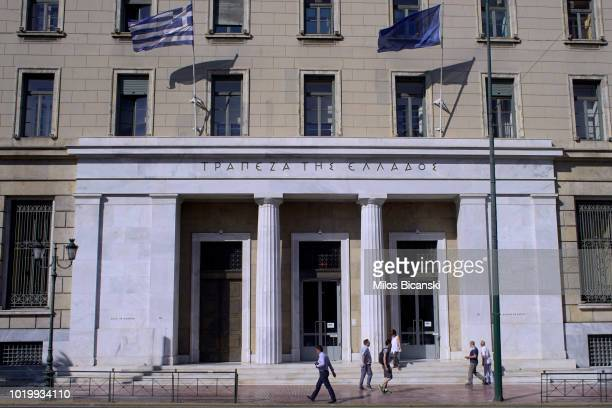 People walk past a derelict building on August 18 2018 in Athens Greece Greece's final bailout officially ends after eight years of hugely unpopular...